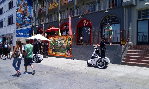 Police patrolling Venice Beach; the Freakshow is in the background