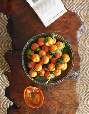A bowl of clementines on a coffee table made from a free-form walnut top. PIN by California Chic.